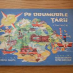 PE DRUMURILE TARII - CINTECE (PARTITURI ) - muzica Th. Bratu, Ilustrati: Livia Rusz, versuri: Petre Ghelmez -- [1967, 45 p, imagini color ] - Carte educativa