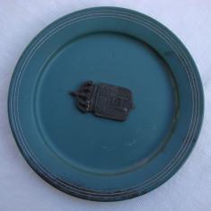Farfurie veche cu patina avand in centru o insigna - Metal/Fonta