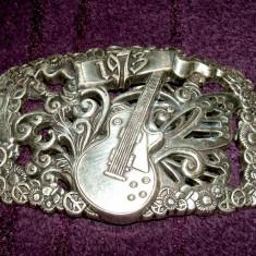 Catarama metalica de curea din 1973 - chitara electrica, miscarea Flower Power