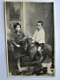 Fotografie veche, interbelica: 2 copii cu calut de lemn. Format CP